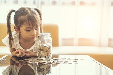 little girl with jar of money