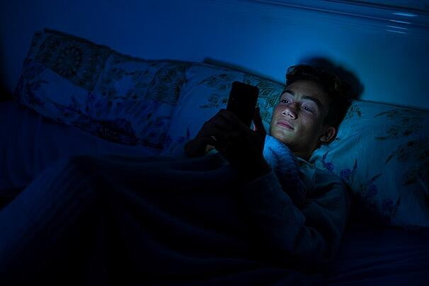 teen in bed on cell phone